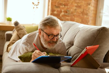 Senior man working with tablet at home - concept of home studying. Caucasian male model lying on sofa and making notes while serfing in internet, watching cinema or webinar, online lessons. Banco de Imagens