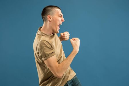 Caucasian young mans half-length portrait on blue studio background. Beautiful male model in shirt. Concept of human emotions, facial expression, sales, ad. Celebrating, crazy happy, screaming.