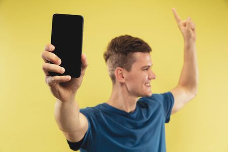 Caucasian young mans half-length portrait on yellow studio background. Beautiful male model in blue shirt. Concept of human emotions, facial expression. Showing phones screen and pointing up. Reklamní fotografie