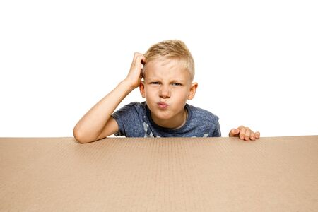 Cute and upset little boy opening the biggest postal package. Disappointed young male model on top of cardboard box looking inside. Gift, present, delivery, shipment, sales, black friday concept.
