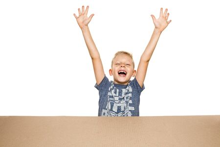 Cute, astonished little boy opening the biggest postal package. Shocked, happy young male model on top of cardboard box looking inside. Gift, present, delivery, shipment, sales, black friday concept.