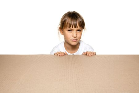 Cute and astonished little girl opening the biggest postal package. Excited young female model on top of cardboard box looking inside. Gift, present, delivery, shipment, sales, black friday concept. Banque d'images
