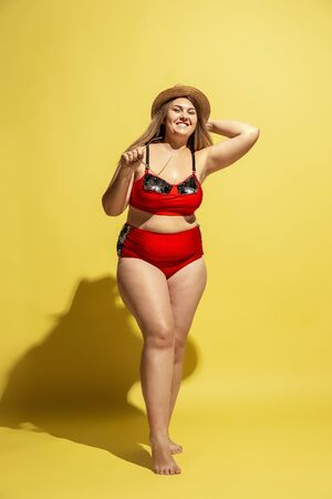 Young caucasian plus size female models preparing for beach resort on yellow background. Woman in red swimsuit, hat and sunglasses. Concept of summertime, party, body positive, equality and chill.