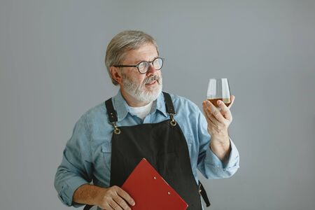 Confident senior man brewer with self crafted beer in glass on wooden barrel on grey background. Owner of factory presented his products, testing quality. Oktoberfest, drink, alcohol, industry. Reklamní fotografie