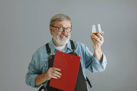 Confident senior man brewer with self crafted beer in glass on wooden barrel on grey background. Owner of factory presented his products of brewing, smiling. Oktoberfest, drink, alcohol, industry.