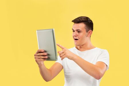Caucasian young mans half-length portrait on yellow studio background. Beautiful male model in shirt. Concept of human emotions, facial expression, sales, ad. Using tablet and looks happy.