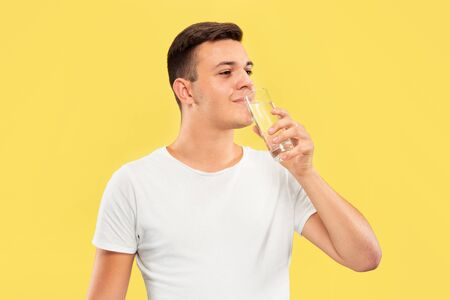 Caucasian young mans half-length portrait on yellow studio background. Beautiful male model in shirt. Concept of human emotions, facial expression, sales, ad. Enjoying drinking pure water. Imagens