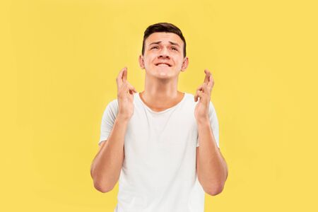 Caucasian young mans half-length portrait on yellow studio background. Beautiful male model in shirt. Concept of human emotions, facial expression, sales, ad. Showing the gesture of good luck.