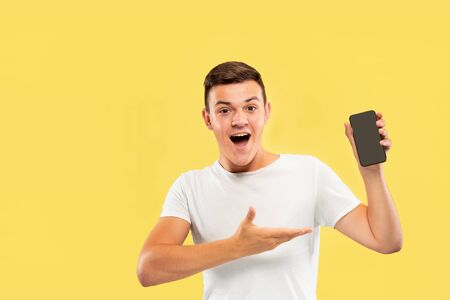 Caucasian young mans half-length portrait on yellow studio background. Beautiful male model in shirt. Concept of human emotions, facial expression, sales, ad. Showing phones screen and smiling. Imagens