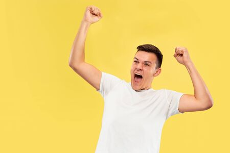 Caucasian young mans half-length portrait on yellow studio background. Beautiful male model in shirt. Concept of human emotions, facial expression, sales, ad. Celebrating, calling, screaming. Imagens