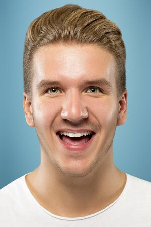 Caucasian young mans close up portrait on blue studio background. Beautiful male model with well-kept skin. Concept of human emotions, facial expression, sales, ad, beauty. Smiling, laughting.
