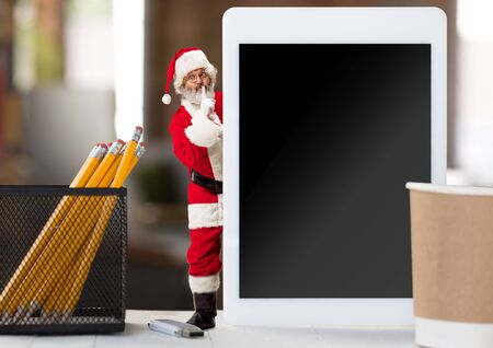 Happy Christmas Santa Claus hiding behind a tablet and whispering a secret. Caucasian male model in traditional holidays costume. Concept of holidays, new years, winter mood, gifts. Copyspace. Reklamní fotografie