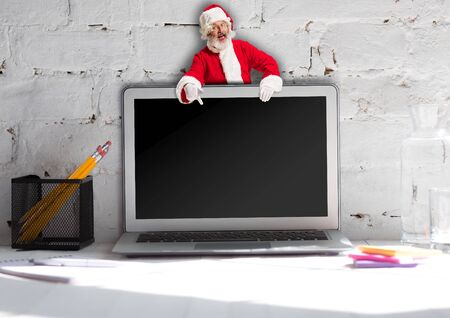 Happy Christmas Santa Claus on top of laptop on white brick wall background. Caucasian male model in traditional holidays costume. Concept of holidays, new years, winter mood, gifts. Copyspace.