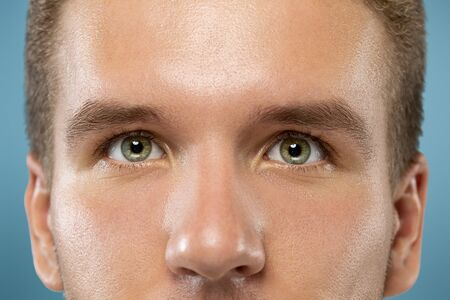 Caucasian young mans close up portrait on blue studio background. Beautiful male model with well-kept skin. Concept of human emotions, facial expression, sales, ad, beauty. Green eyes looking up.
