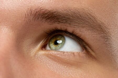 Caucasian young mans close up portrait. Beautiful male model with well-kept skin. Concept of human emotions, facial expression, sales, ad, beauty, hope. Green eye looking up and eyebrow.