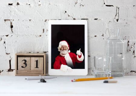 Happy Christmas Santa Claus with tablet on white brick wall background. Caucasian male model in traditional holidays costume. Concept of holidays, new years, winter mood, gifts. Copyspace. Reklamní fotografie