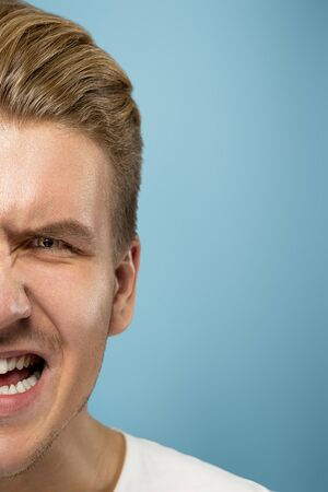 Caucasian young mans close up portrait on blue studio background. Beautiful male model with well-kept skin. Concept of human emotions, facial expression, sales, ad, beauty. Angry screaming. Imagens