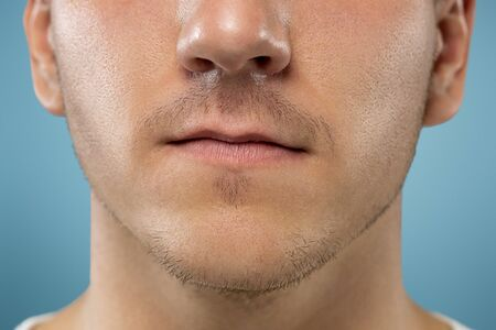 Caucasian young mans close up portrait on blue studio background. Beautiful male model with well-kept skin. Concept of human emotions, facial expression, sales, ad, beauty. Lips and cheeks.