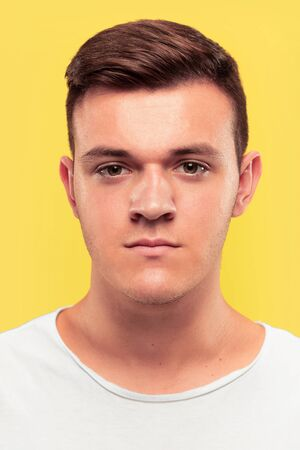 Caucasian young mans close up portrait on yellow studio background. Beautiful male model with well-kept skin. Concept of human emotions, facial expression, sales, ad. Looks serious and calm.