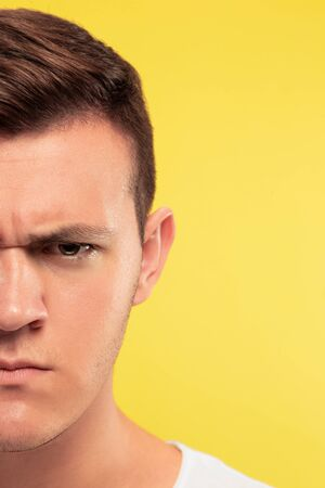 Caucasian young mans close up portrait on yellow studio background. Beautiful male model with well-kept skin. Concept of human emotions, facial expression, sales, ad. Looks angry, serious. Imagens