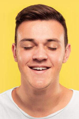Caucasian young mans close up portrait on yellow studio background. Beautiful male model with well-kept skin. Concept of human emotions, facial expression, sales, ad. Smiling with eyes closed. Imagens