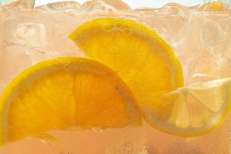 Close up of lemon slices in lemonade and ice cubes background. Texture of cooling sweet summers drink with macro bubbles on the glass wall. Fizzing or floating up to top of surface.