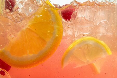 Close up of lemon slices and cherry in lemonade and ice cubes background. Texture of cooling sweet summers drink with macro bubbles on the glass wall. Fizzing or floating up to top of surface. Stockfoto