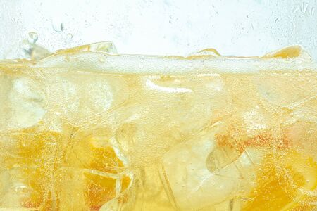 Close up of lemon slices in stirring the lemonade and ice cubes on background. Texture of cooling sweet summers drink with macro bubbles on the glass wall. Fizzing or floating up to top of surface.