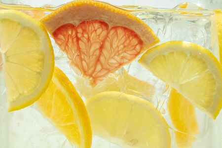 Close up of lemon and grapefruit slices in lemonade and ice cubes background. Texture of cooling sweet summers drink with macro bubbles on the glass wall. Fizzing or floating up to top of surface.