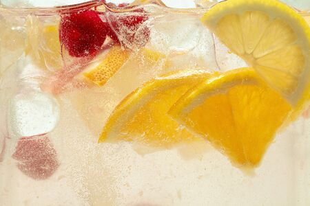 Close up of lemon slices and cherry in lemonade and ice cubes background. Texture of cooling sweet summers drink with macro bubbles on the glass wall. Fizzing or floating up to top of surface. Фото со стока