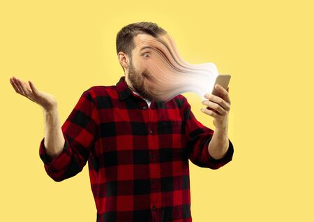 Young man using smartphone isolated on yellow studio background. Concept of human emotions, facial expression, sales, ad, engagement by gadget, social media, immersion in vlogging, blogging. Copyspace.