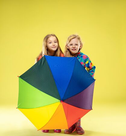 A full length portrait of a bright fashionable girls in a raincoat holding an umbrella of rainbow colors on yellow studio background. Autumn and spring fashion for kids. Cute stylish blonde girls.