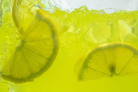 Close up view of the lemon slices in lemonade background. Texture of cooling sweet summers drink with macro bubbles on the glass wall. Fizzing or floating up to top of surface.