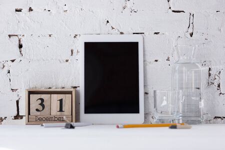 Mock up empty black tablet screen on the brick wall  with pencils and bottle of water.