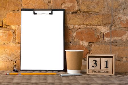 Mock up blank empty picture or sheet on the brown brick wall  with coffee cup and pencils.