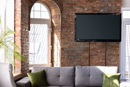 Mock up blank empty television screen on the brown brick wall  with sofa and sunlight.