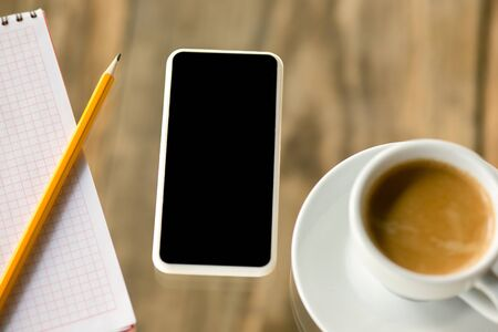 Mock up empty black smartphone screen on wooden table  with pencils, notes and cup of coffee. Stock Photo