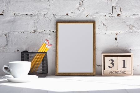 Mock up blank empty picture or sheet on the white brick wall  with cup of coffee and pencils.