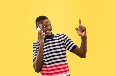 Breathtaking conversation. Young african-american man with smartphone pointing at negative space isolated on yellow studio background, facial expression. Beautiful male half-lenght portrait. Concept of human emotions, facial expression.