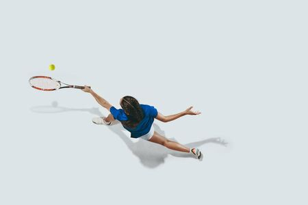 Young woman in blue shirt playing tennis. She hits the ball with a racket. Indoor studio shot isolated on white. Youth, flexibility, power and energy. Negative space. Top view. Foto de archivo