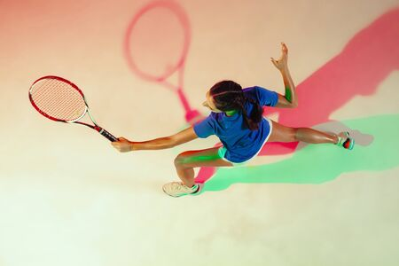 Young woman in blue shirt playing tennis. She hits the ball with a racket. Indoor studio shot with mixed light. Youth, flexibility, power and energy. Top view. Foto de archivo