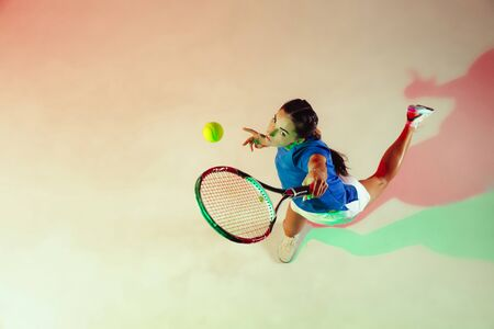 Young woman in blue shirt playing tennis. She hits the ball with a racket. Indoor studio shot with mixed light. Youth, flexibility, power and energy. Top view.