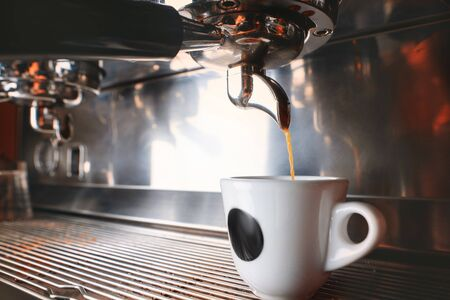Start your day with cup of aromatic drink. Stylish black espresso making machine brewing coffee, shooted in cafe.