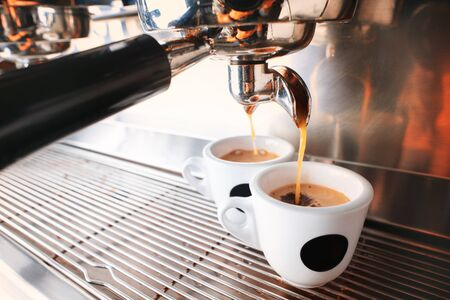 Start your day with cup of aromatic drink. Stylish black espresso making machine brewing two cups of coffee, shooted in cafe.