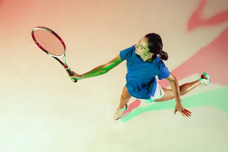 Young woman in blue shirt playing tennis. She hits the ball with a racket. Indoor studio shot with mixed light. Youth, flexibility, power and energy. Top view. Reklamní fotografie