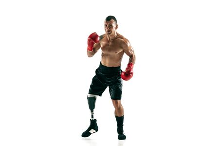 Full length portrait of muscular sportsman with prosthetic leg, copy space. Male boxer in red gloves. Isolated shot on white studio background.
