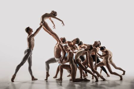 The group of modern ballet dancers. Contemporary art ballet. Young flexible athletic men and women in ballet tights. Studio shot isolated on white background. Negative space.
