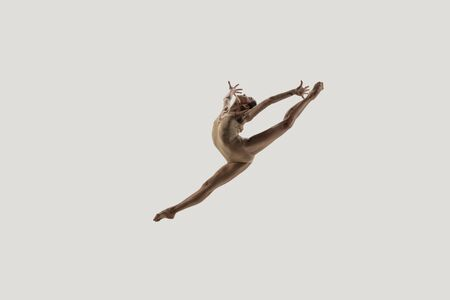 Modern ballet dancer. Contemporary art ballet. Young flexible athletic woman.. Studio shot isolated on white background. Negative space.
