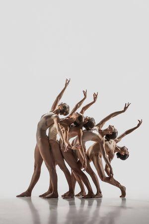 De groep moderne balletdansers. Hedendaags kunstballet. Jonge flexibele atletische mannen en vrouwen in balletpanty's. Studio opname geïsoleerd op een witte achtergrond. Negatieve ruimte.