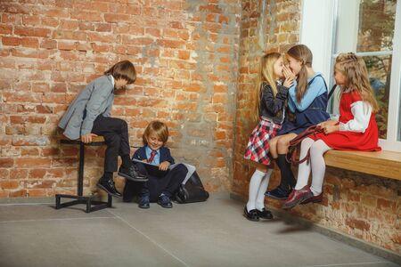 Group of kids spending time after school together. Handsome friends resting after classes before start of doing homework. Modern loft interior. Schooltime, friendship, education, togetherness concept.